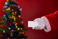 拿着一个白色空插件的圣诞老人有益于与装饰的圣诞树的文本 免版税图库摄影