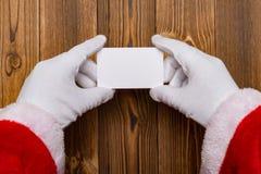 拿着一个白色空插件的圣诞老人有益于文本 库存图片