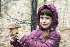 拿着一个白色蘑菇的女孩 库存照片