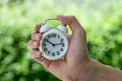 拿着一个白色闹钟的手当企业或时间读秒 库存图片
