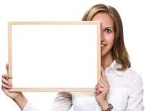 拿着一个白色黑板的美丽的白肤金发的妇女 免版税库存照片