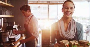 拿着一个盘子用在café的三明治的女服务员 影视素材