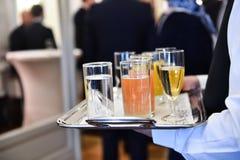 拿着一个盘子用饮料的侍者在鸡尾酒会期间 免版税库存图片