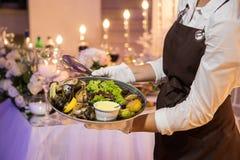 拿着一个盘用海鲜和菜的女服务员 库存照片