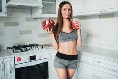 拿着一个碗草莓和一杯的性体育女孩圆滑的人在厨房里 库存照片