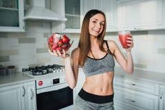 拿着一个碗草莓和一杯的性体育女孩圆滑的人在厨房里 库存图片