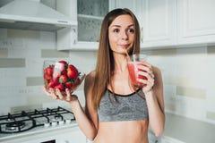 拿着一个碗草莓和一杯的性体育女孩圆滑的人在厨房里 免版税库存照片