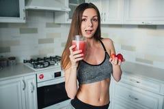 拿着一个碗草莓和一杯的性体育女孩圆滑的人在厨房里 免版税图库摄影