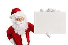 拿着一个空插件的惊奇的圣诞老人 库存图片