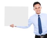 拿着一个空白广告牌的商人 免版税库存照片