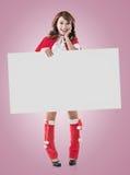 拿着一个空白的委员会的圣诞节女孩 免版税图库摄影