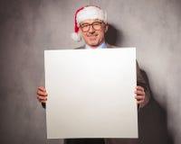 拿着一个空白的委员会的微笑的圣诞老人商人 免版税库存照片