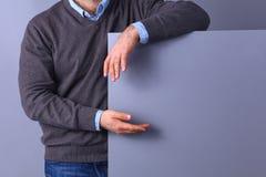 拿着一个空白的委员会的年轻商人,站立在灰色背景 库存照片
