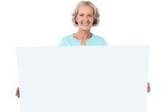 拿着一个空白的广告牌的偶然老妇人 免版税图库摄影