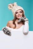 拿着一个空白的广告牌的美丽的冬天妇女被隔绝 免版税库存照片