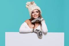 拿着一个空白的广告牌的美丽的冬天妇女被隔绝 图库摄影