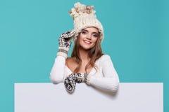 拿着一个空白的广告牌的美丽的冬天妇女被隔绝 免版税图库摄影
