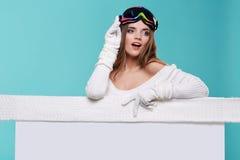 拿着一个空白的广告牌的美丽的冬天妇女 图库摄影