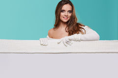 拿着一个空白的广告牌的美丽的冬天妇女 免版税库存图片