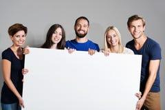 拿着一个空白的标志的企业队 免版税库存照片