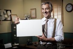 拿着一个空白的标志的微笑的葡萄酒商人 免版税库存照片
