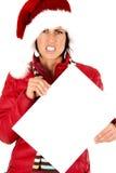 拿着一个空白的标志的被注重的女性模型戴圣诞老人的帽子 免版税库存照片