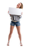 拿着一个空白的白板的性感的妇女提出某事 免版税库存图片