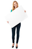 拿着一个空白的白板的愉快的妇女 免版税库存照片