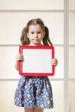 拿着一个空白的磁性委员会的传神小女孩 免版税图库摄影