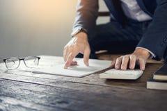 拿着一个空白的笔记本的商人和计算赞成事务 库存照片