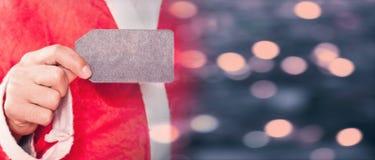 拿着一个空白的销售标签的圣诞老人 库存图片