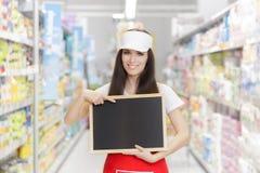 拿着一个空白的黑板的微笑的超级市场雇员 免版税库存图片