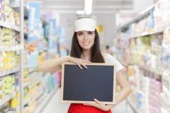 拿着一个空白的黑板的微笑的超级市场雇员 免版税图库摄影