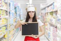 拿着一个空白的黑板的惊奇的超级市场雇员 免版税库存照片