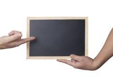拿着一个空白的黑板的手 库存照片