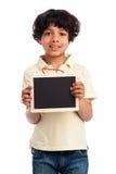 拿着一个空白的黑板的逗人喜爱的混合的族种男孩。 图库摄影