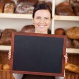 拿着一个空白的黑板的面包店工作者 免版税库存照片