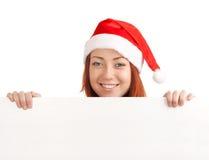 拿着一个空白符号的圣诞老人帽子的年轻人 库存照片