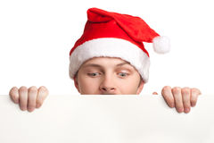 拿着一个空白符号的圣诞老人帽子的年轻人 图库摄影