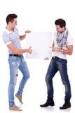 拿着一个空白董事会的二个年轻人 免版税图库摄影