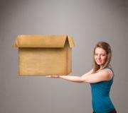 拿着一个空的纸板箱的少妇 免版税图库摄影