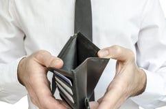 拿着一个空的钱包的人 免版税库存照片