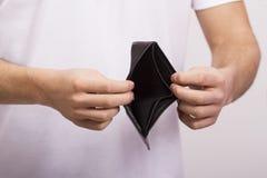 拿着一个空的钱包的人 图库摄影