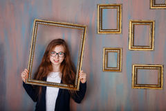 戴拿着一个空的画框的眼镜的青少年的女孩 免版税库存图片