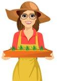 戴拿着一个箱子新鲜的绿色幼木植物的眼镜的年轻农夫妇女 免版税库存照片