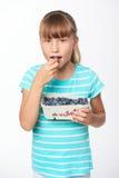 拿着一个箱子用越桔和吃它的小女孩 免版税库存照片