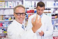拿着一个箱子药片的微笑的药剂师 免版税库存照片