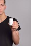 拿着一个箱子药片的年轻人的面孔的一半在他的手上 免版税库存照片