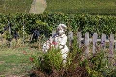 拿着一个篮子用在葡萄园背景的葡萄的男孩的雕象在圣Emilion地区 免版税图库摄影