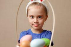 拿着一个篮子用复活节彩蛋的小女孩佩带的兔宝宝耳朵 免版税库存照片